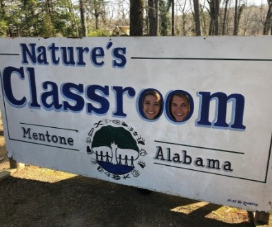 Natures Classroom sign with teachers looking through letters