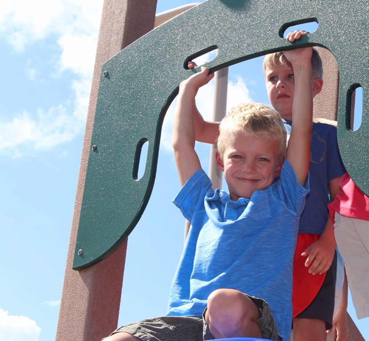 students on playground at the top of the slide