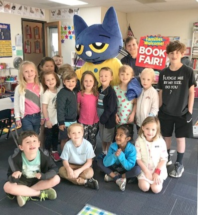 group of young students with book fair Pete the cat