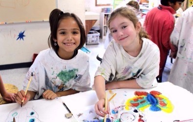 two girls painting in art class