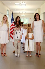 PreK and Kindergarten students with teachers in promotion procession line with flag and cross