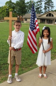 lower primary boy and girl with flag and cross before promotion
