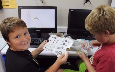 two boys working on computer explorers software