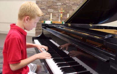 boy playing steinway piano