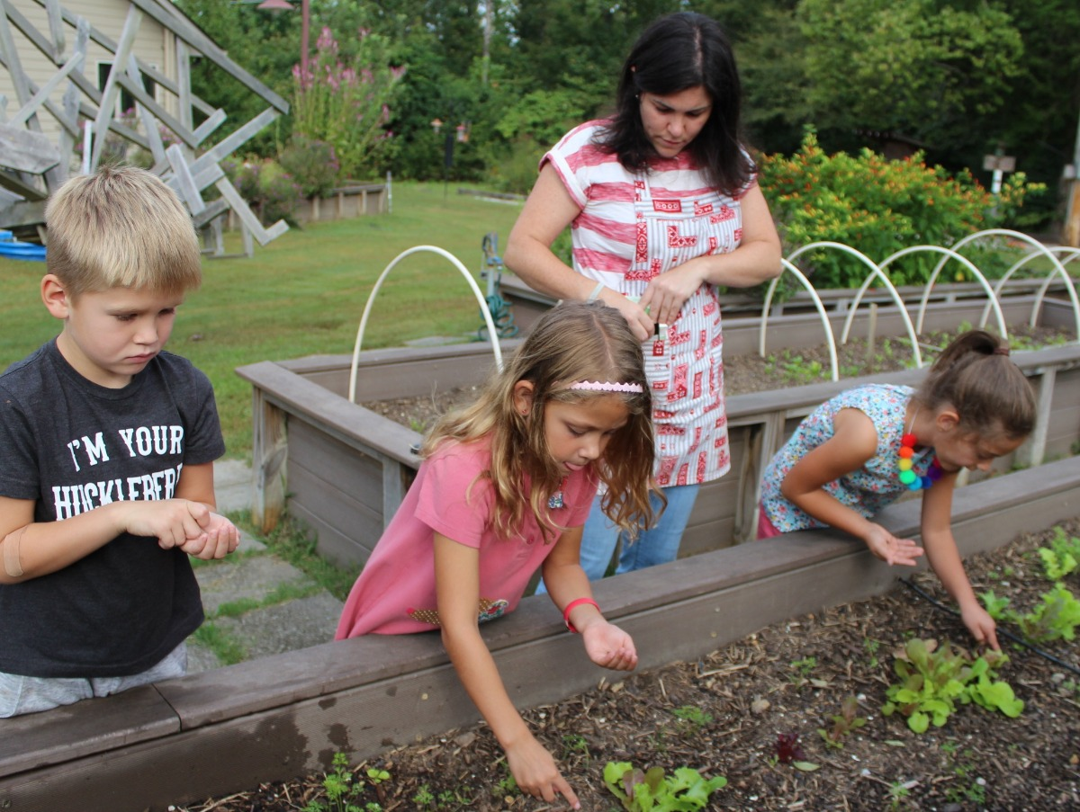 young chldren planting seeds in the campus garden