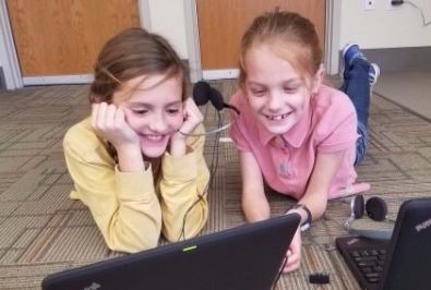 two girls on floor with laptop