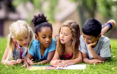 group one boy and three girls reading outside on grass summer reading