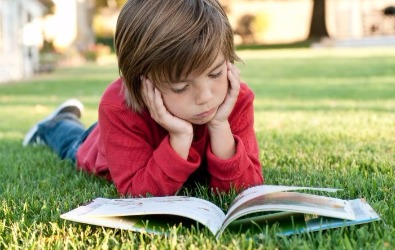 boy reading outside on grass summer reading